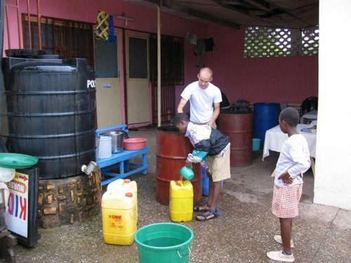 When it rains, tin barrels are rolled out to catch water. Once full, water is moved to smaller bins for storage. We use rain water to bathe, cook, clean, flush toilet & laundry.