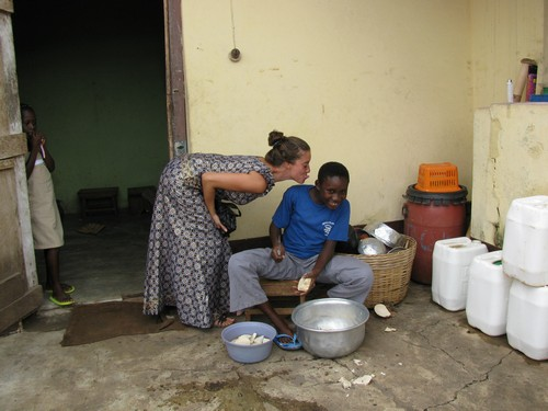 Jaymie with Faustina at the family house after Sunday mass. Faustina is preparing banku, mashed up maize & cassava (type of yam)