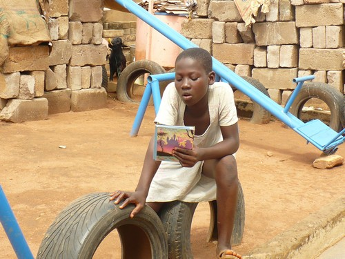 Abigail (class 2) reading on a tire next to the foundation of what will be the new library. LETS GET THAT LIBRARY!!