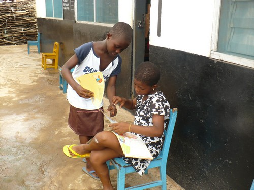 Augustina (class 2) asking Patience (class 3) for help with a word she doesn't understand.
