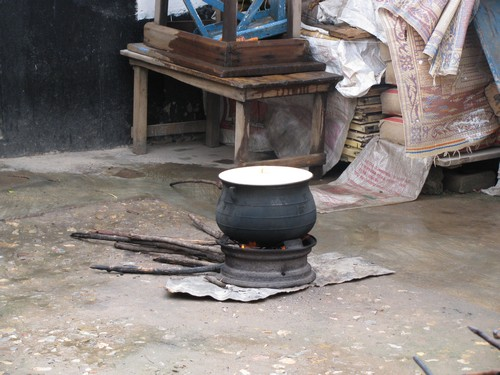 A pot on the good old fire. To keep the fire hot enough, we fan it constantly with a thick woven fan.